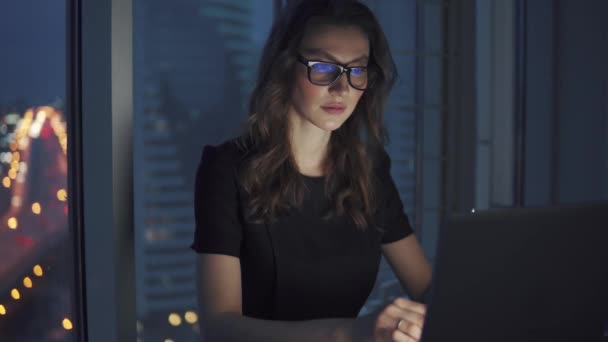 work late at night in the office. young woman in business suit and glasses works on a laptop on the background of night city lights.