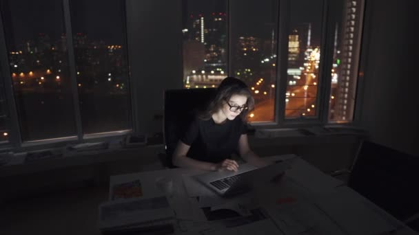 manager works until late in the office. young female entrepreneur working on a laptop late at night against the lights of the night city.