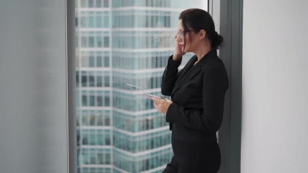 Üzletasszony használ egy mozgatható telefon rövid idő álló az ablakon-ból egy felhőkarcoló