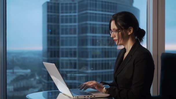 mladá žena pracující na laptopu, sedící u okna v kanceláři