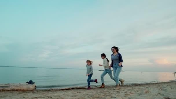mladá matka se s dětmi baví venku. děti a matka utílejí podél pobřeží při západu slunce.