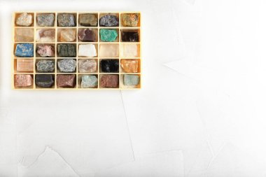 Set of minerals, a collection of rocks, minerals in the box on white cement background.