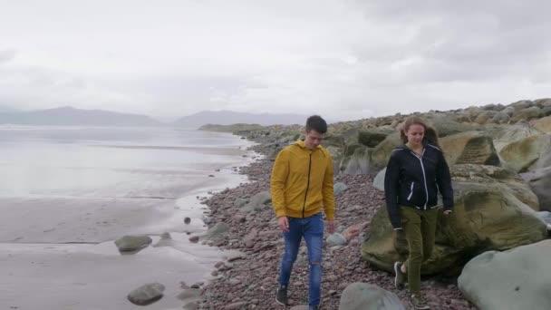 Two friends walk along the rocks of Rossbeigh beach