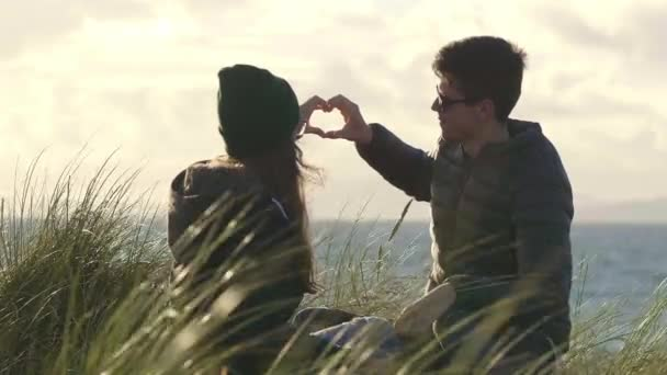 Young couple in love forms the shape of a heart with their hands