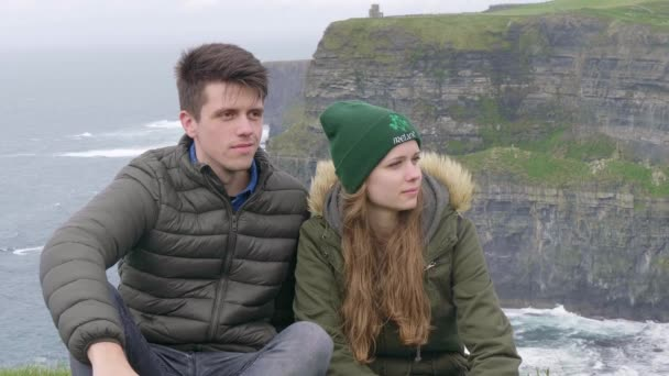 Couple in love relaxes at the Cliffs of Moher