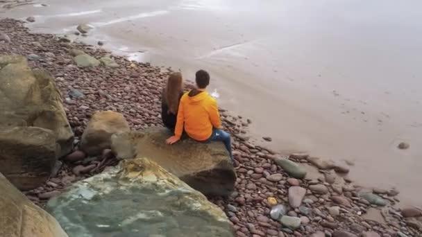 Couple sits on a rock near the ocean