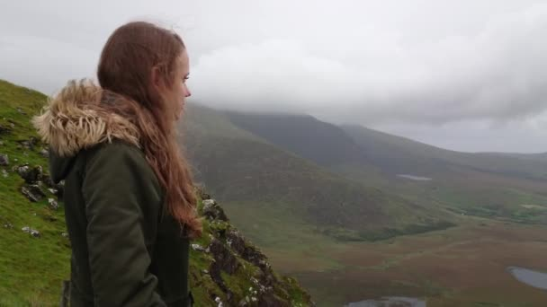 Young woman is impressed by the amazing landscape of Ireland