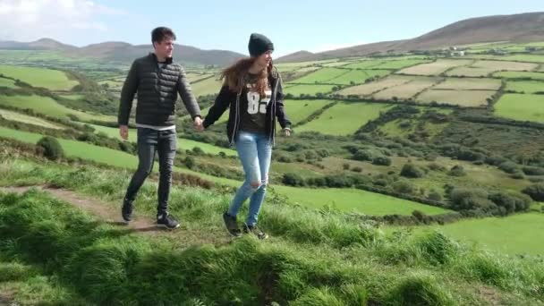 Pretty girl drags her boyfriend through the amazing landscape in Ireland