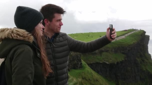 Happy couple tries to take selfies on a windy day at the Cliffs of Moher
