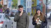 Two friends in the city center of Dingle eat ice cream