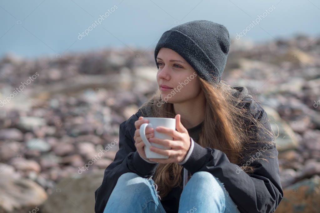 Young woman with a cup of coffee in her hands sits on rocks