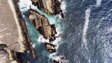 Aerial view over blue ocean water and the rocky coast if Ireland