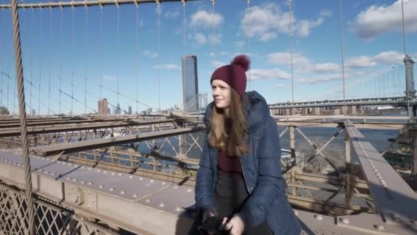 Young beautiful woman relaxes on Brooklyn Bridge while enjoying the amazing view