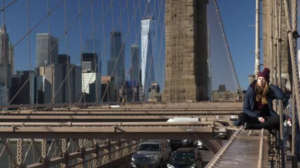 Krásná dívka na Brooklyn Bridge má za slunečného dne při odpočinku