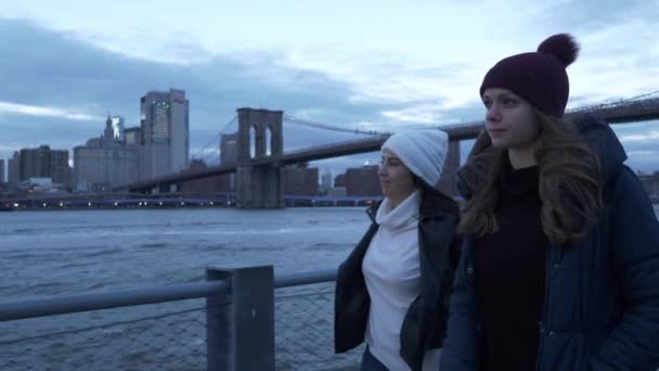 Two friends walk along the amazing skyline of Manhattan in the evening