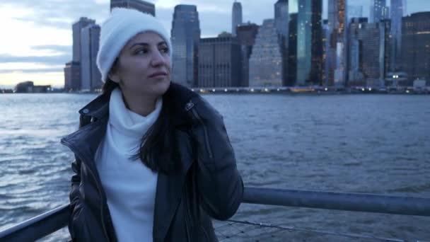 Mladá žena chodí podél nádherné panorama Manhattanu večer