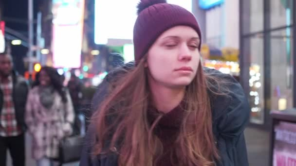 Beautiful girl walks through the city of New York at Times Square by night