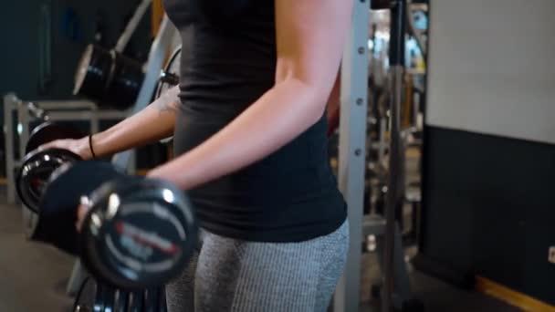 Fiatal és szexi lány egy tornateremben - súlyzós edzés