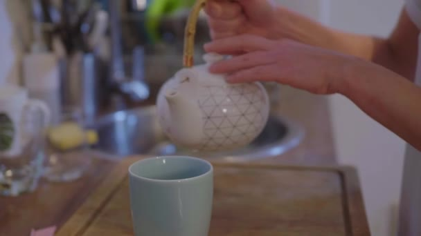 Filling hot tea into a cup in the kitchen close up shot