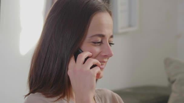 Hezká žena bere telefonní hovor v jejím obývacím pokoji