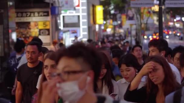Crowd of people walking through Shibuya at night - TOKYO, JAPAN - JUNE 12, 2018