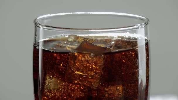 Amazing close up shot of a glas of Cola with ice cubes - refreshing soda in slow motion