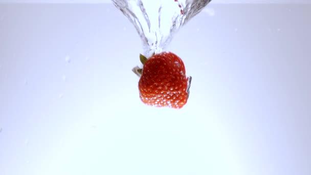Čerstvé jahody spadnout do vody - zpomalený záběr
