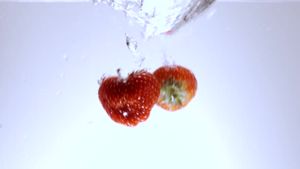 Fresh strawberries fall into water - slow motion shot
