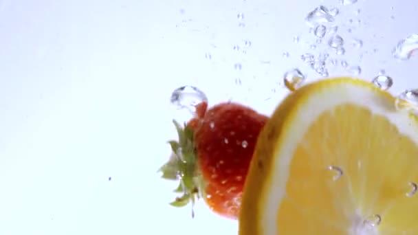 Jahody a pomeranče v čisté vodě