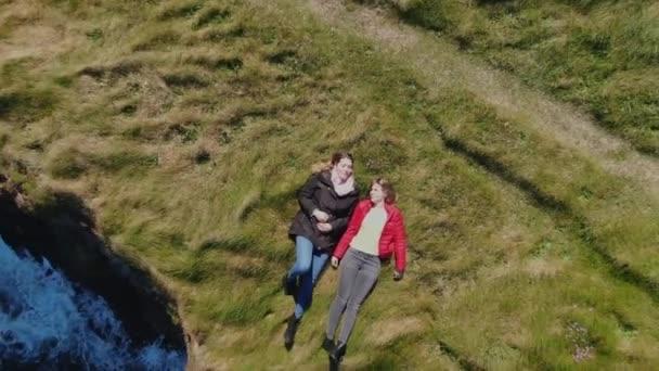 zwei Mädchen liegen im Gras an den Klippen der irischen Küste - Drohnenblick von oben