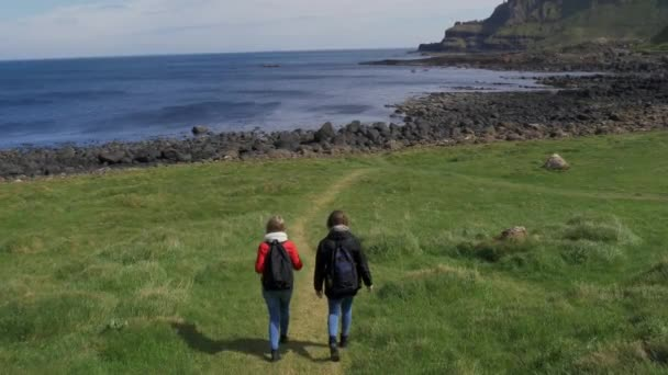 Two girls walk along edge of famous Cliffs of Moher