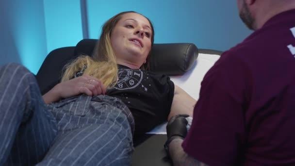 junge Frau lässt sich in einem Tattoo- und Piercing-Studio tätowieren