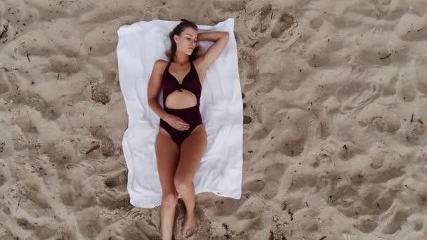 Sexy dívka opalování na písečné pláži - letecké drone záběry