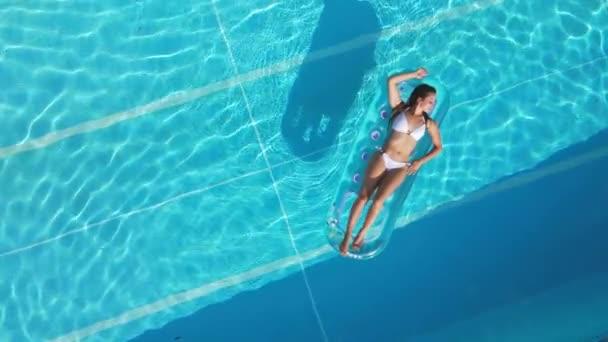 Csinos lány fekszik egy matracon a medencében.