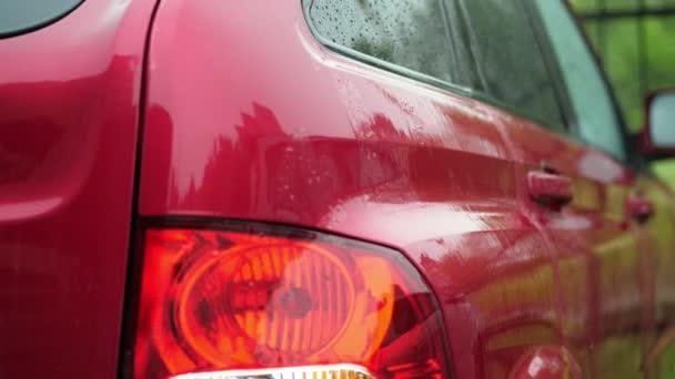 Blick von außen, dort ist starker Regen Dusche, schwere Tropfen fallen mit Wasser spritzt auf nassem Untergrund des roten Autos stehen auf Parkplatz. close-up, Rücklicht. Wassertropfen auf Autotüren