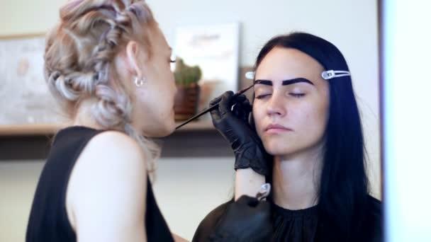 la giovane donna ottiene la procedura di correzione delle sopracciglia. kosmetolog-make-up artist si applica la vernice con il pennello sulle sopracciglia nel salone di bellezza. Assistenza professionale per il viso