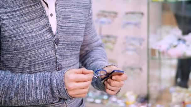 muž má skřipec brýle z malé případu, pokusy na nich. portrét pohledný mladý muž výběru brýlí v maloobchodě optik. zdravotní péče koncept