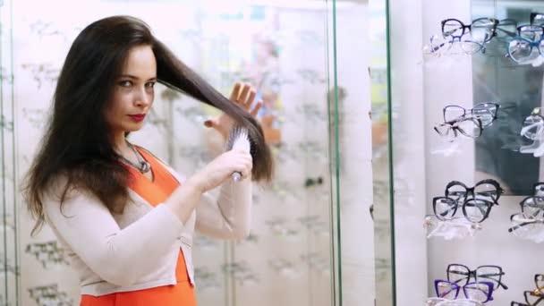 krásná žena, česání tmavé dlouhé vlasy kulatý hřebenem