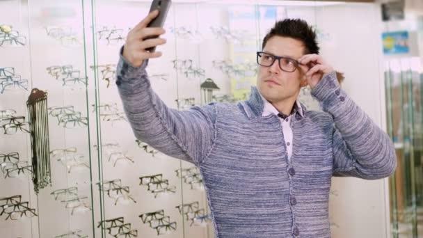 sexy pohledný mladý muž v brýlích, brýle dělá selfie na partnerském obchodě, optika, optik maloobchodě, brýle shop, muž zíral na kameru v jeho mobilní telefon
