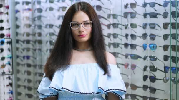 sexy krásná žena zírala na kamery. Portrét usmívající se žena zákazníků nosit brýle v partnerském obchodě, optické uprostřed. mnoho sklenic na pozadí