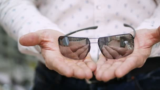 close-up, mens hands hold a sunglasses, spectacles. the man is dressed in a white shirt. health care concept