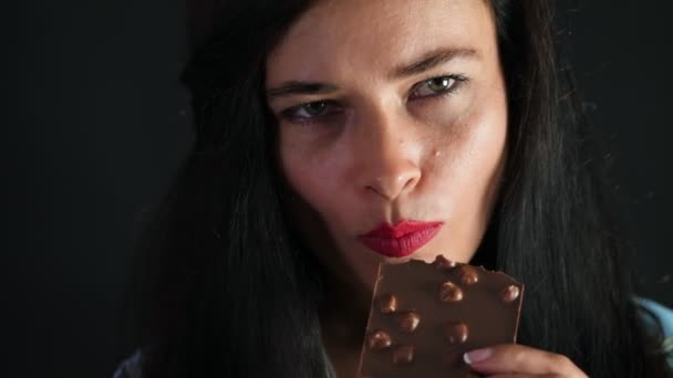 Porträt einer sexy brünetten Frau mit roten Lippen, die erotisch und verspielt schwarze Schokolade mit Haselnüssen isst und im Studio in die Kamera schaut. dunkelgrauer Hintergrund.