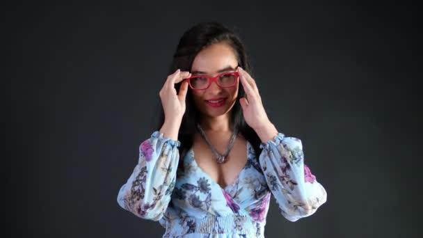portrét sexy bruneta žena s červenou kdo eroticly rty a hravě se snaží na stylové brýle, brýle a sexuálně při pohledu na fotoaparát, pózuje ve studiu. tmavě šedé pozadí