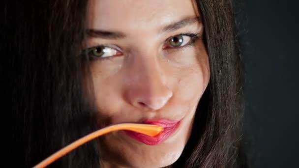 portrét sexy bruneta žena s červenou kdo eroticly rty a hravě se snaží na stylové brýle, brýle a sexuálně při pohledu na fotoaparát ve studiu. tmavě šedé pozadí.