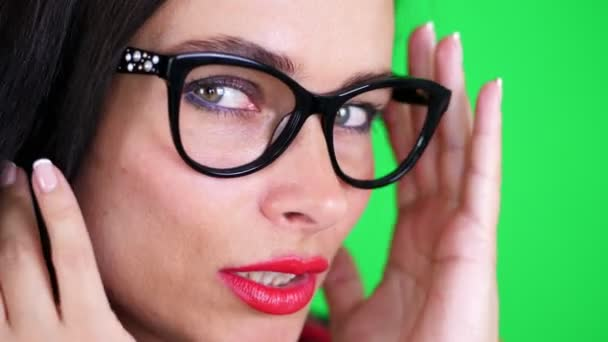 green background, chromeakey. portrait of a sexy brunette woman with red lips, in stylish glasses, spectacles, eroticly, playfully moves, looking sexually at camera, posing in studio.