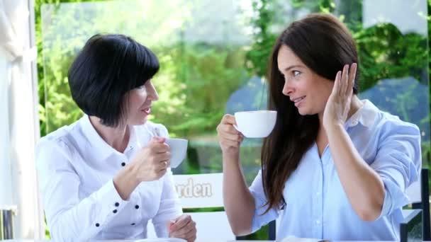 v létě na terase v kavárně, dvě krásné Brunetky čtyřicet let ženy jsou chatování roztomilý, jsou oblečeni v blond halenky