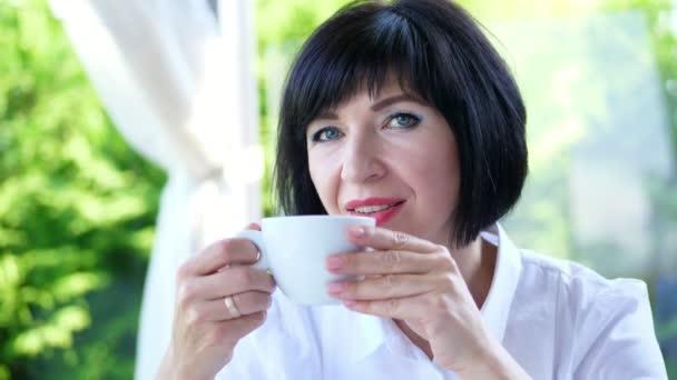Portrét příjemným úsměvem, Happy krásná skutečná 40 let ukrajinská žena. žena pití káva, čaj, z bílého hrnečku
