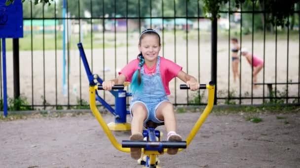 lächelnd, glücklich achtjähriges Mädchen engagiert, macht Übungen auf Outdoor-Trainingsgeräten, im Freien, im Park, Sommer, heißer Tag in den Ferien.
