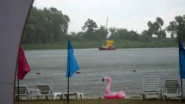 Sommerregen, Gewitter, Starkregen am Strand, am Fluss. Einsam stehen leere Liegestühle und Sonnenschirme, jemand hat einen aufblasbaren Kreis in Form eines rosa Flamingos vergessen..
