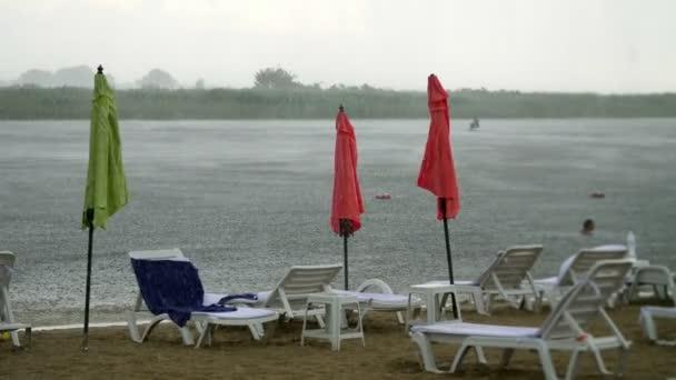 Sommerregen, Gewitter, Starkregen an einem leeren Strand, am Fluss. Einsam stehen Liegestühle und Sonnenschirme, starker, böiger Wind,